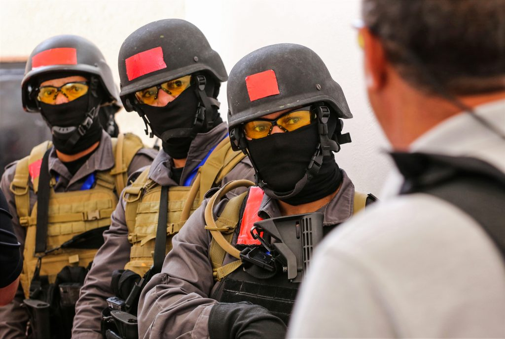 Three people in helmets and flak jackets facing another person (© Raad Adayleh/AP Images)