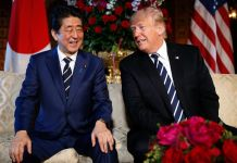Shinzō Abe and Donald Trump sitting on a white couch in front of flags (© Pablo Martinez Monsivais/AP Images)