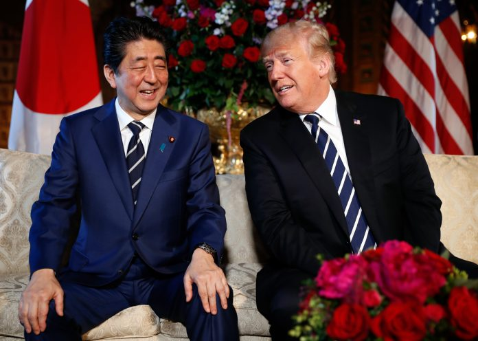 Shinzō Abe y Donald Trump sentados sobre un sofá blanco con banderas de fondo (© Pablo Martinez Monsivais/AP Images)