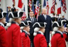 Macron and Trump walking past military guard (© Pablo Martinez Monsivais/AP Images)