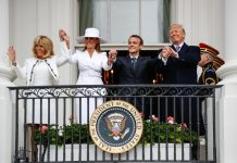 Four people waving from balcony (© Pablo Martinez Monsivais/AP Images)