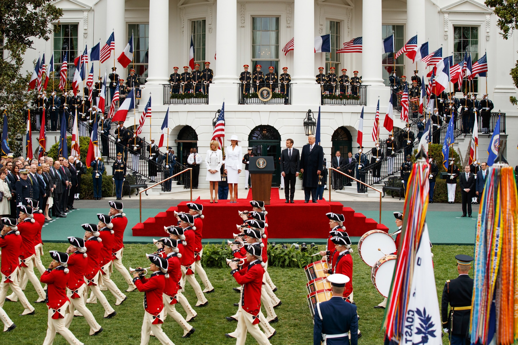 A band marching on the South Lawn of the White House as Presidents Trump and Macron, their wives and others look on (© Evan Vucci/AP Images)