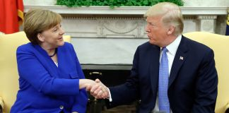 Angela Merkel and Donald Trump, seated and shaking hands (© Evan Vucci/AP Images)
