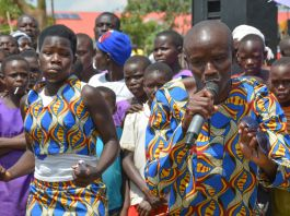 Man singing in front of crowd standing behind him (PMI Uganda IRS Project)