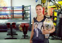 Une femme dans un gymnase tenant une ceinture de championne (© Earl Gibson III/WireImage/Getty Images)