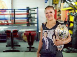 Mujer en un gimnasio sostiene un cinturón trofeo de campeonato (© Earl Gibson III/WireImage/Getty Images)