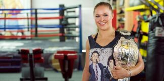 Woman in gym holding championship belt (© Earl Gibson III/WireImage/Getty Images)