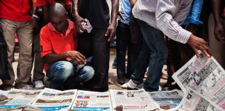 People gathered around newspaper pages on ground (© Eduardo Soteras/AFP/Getty Images)