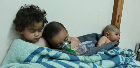 Three small children huddling in a bed with a blue blanket (© Hamza al-Ajweh/AFP/Getty Images)