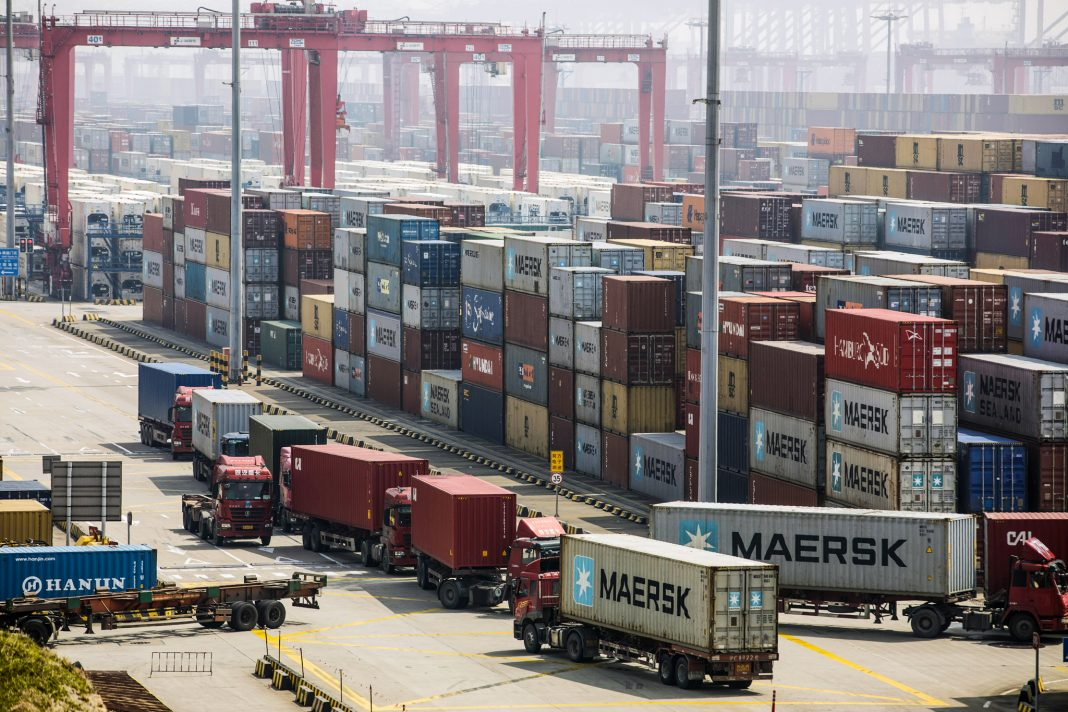 View of port with trucks and stacks of large shipping containers (© Qilai Shen/Bloomberg/Getty Images)