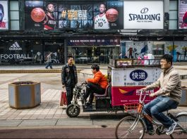 Man riding a bike past a man on a motorized cart who is talking to another man (© Gilles Sabri/Bloomberg/Getty Images)