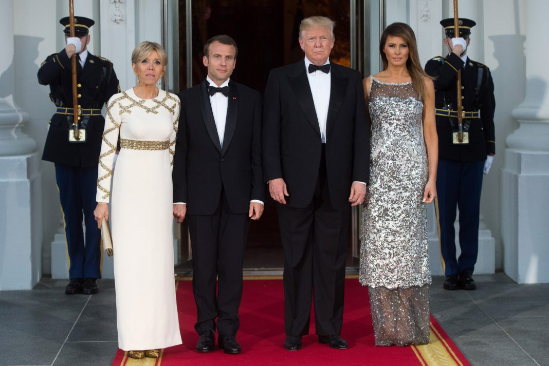 Presidents Macron and Trump and their wives standing on a red carpet at the White House (© Saul Loeb/AFP/Getty Images)