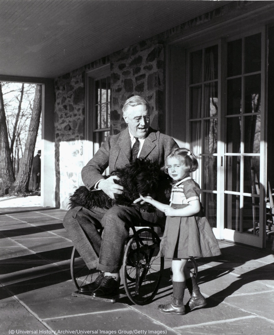 Man sitting on a porch in wheelchair with a dog on his lap and a young girl at his side