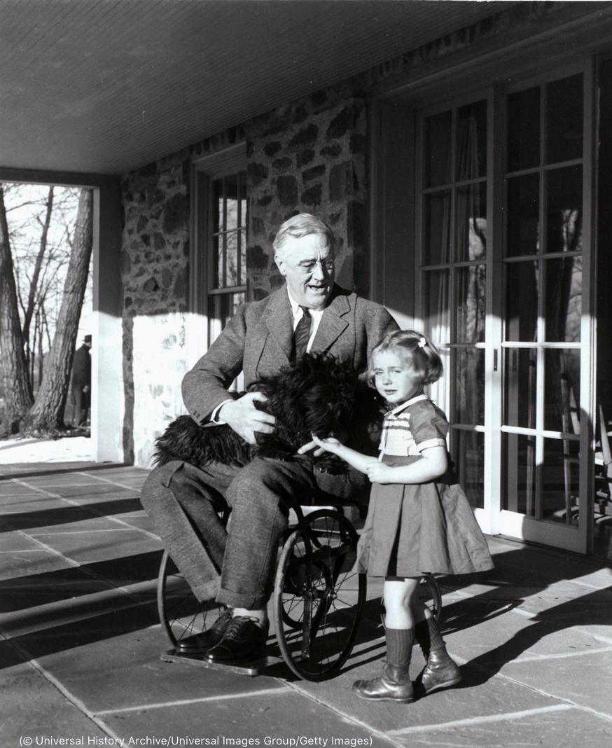 Un hombre en un porche sentado en una silla de ruedas con un perro en su regazo y una niña pequeña a su lado. (© Universal History Archive/UIG via Getty Images)