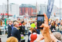Hand holding up mobile phone to take picture of crowd (© Shutterstock)