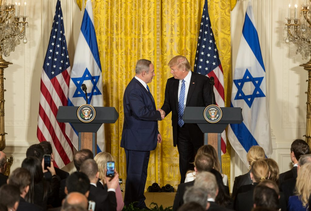 Netanyahu and Trump shaking hands on podium as audience looks on (Official White House Photo/Leslie N. Emory)