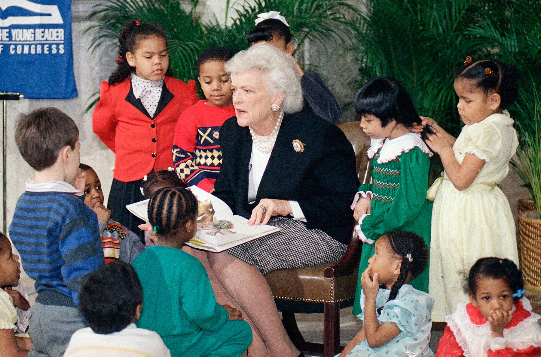 Barbara Bush sitting in a chair reading to children (© Charles Tasnadi/AP Images)