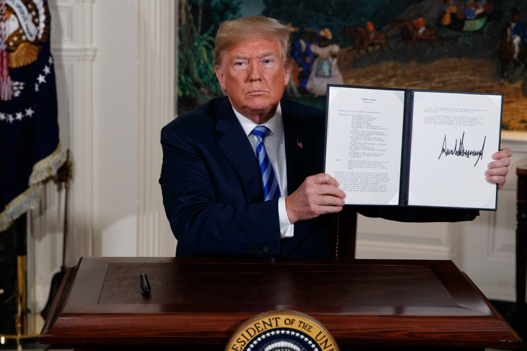 Donald Trump holding up a proclamation (© Evan Vucci/AP Images)