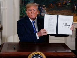 Donald Trump holding up a proclamation (© Evan Vucci/AP Images)