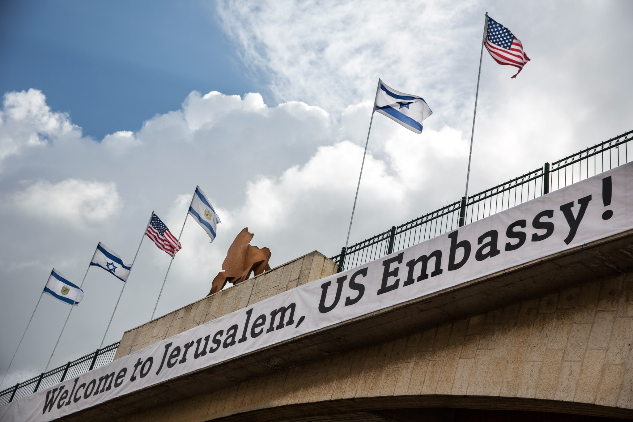 Flags and a sign on a bridge (© Ariel Schalit/AP Images)