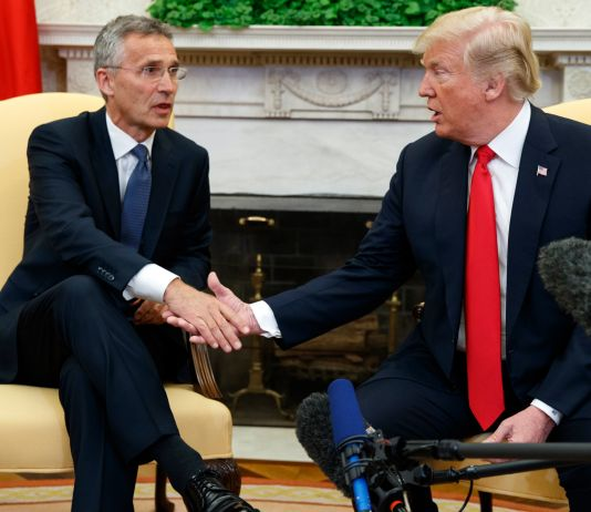 Jens Stoltenberg and President Trump seated and shaking hands (© Evan Vucci/AP Images)