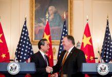 Mike Pompeo et Wang Yi se serrant la main, avec des drapeaux en arrière-plan (© Andrew Harnik/AP Images)