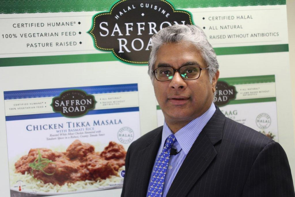 Adnan Durrani standing in front of an enlarged label from one of his packaged products (© American Halal Company)