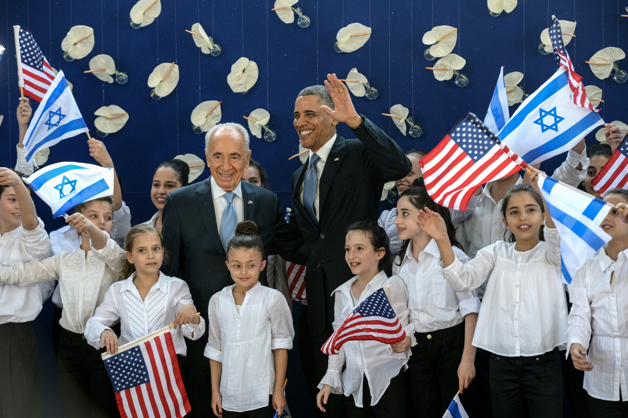 President Obama and a man standing amongst children (State Dept.)