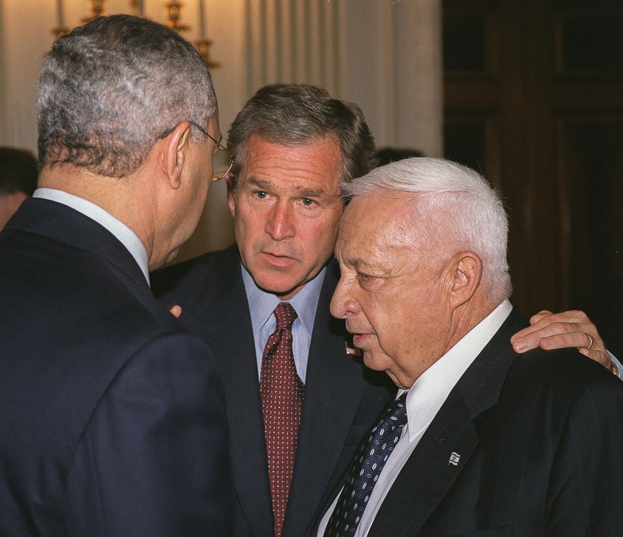 President George W. Bush and two men talking closely (State Dept.)