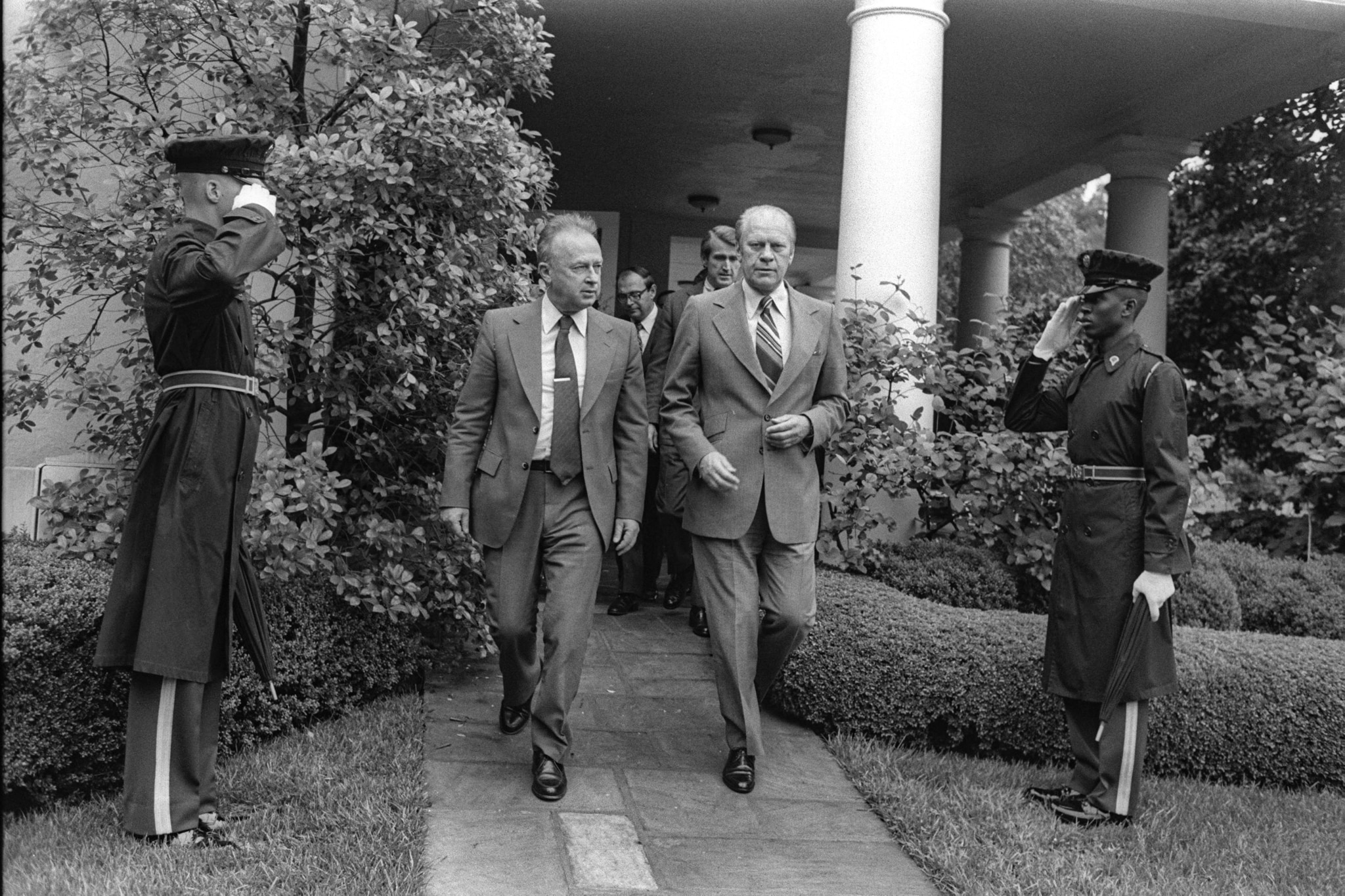 President Ford and others walking out of White House past two saluting men in uniform (State Dept.)