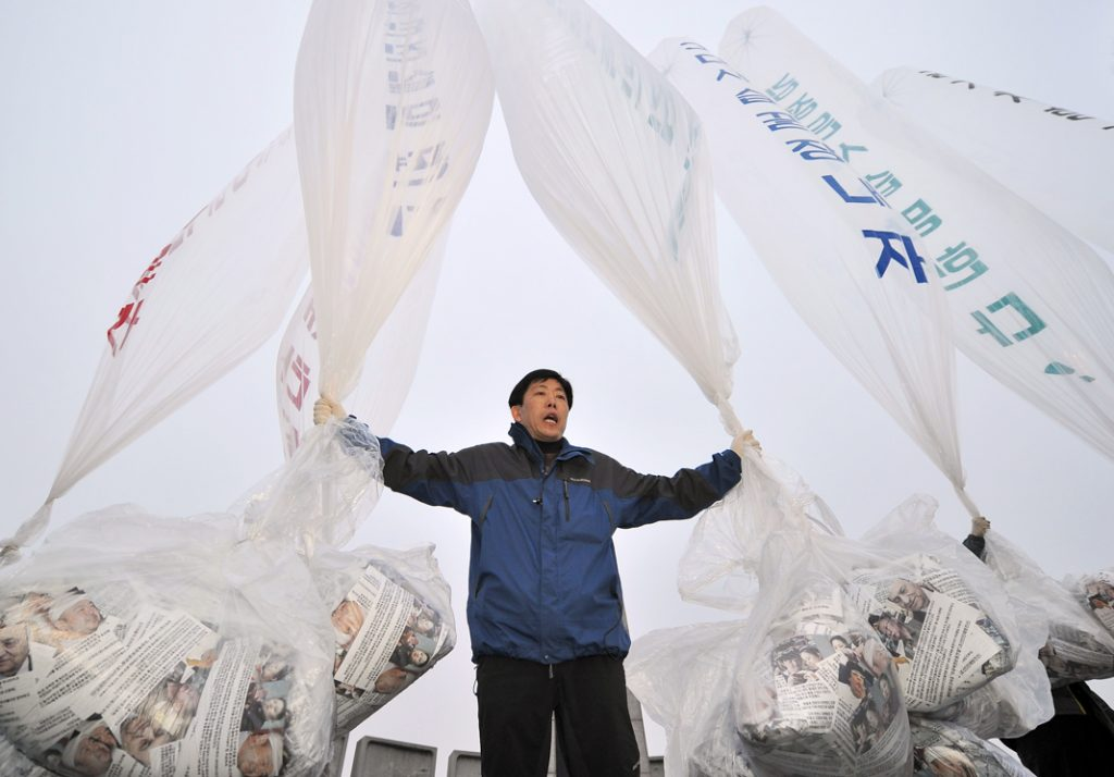 Man holding arms outstretched by large balloons (© Jung Yeon-Je/AFP/Getty Images)