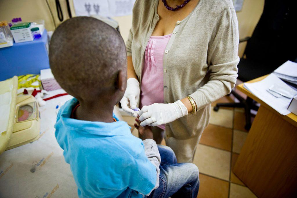 Niño pequeño atendido por una trabajadora médica (© Foto24/Gallo Images/Getty Images)