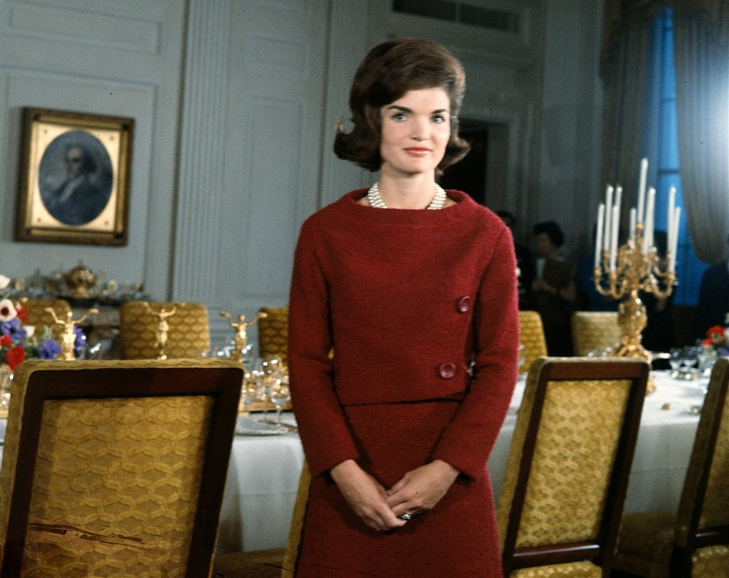 Jacqueline Kennedy standing next to a dining table in the White House (© CBS Photo Archive/Getty Images)