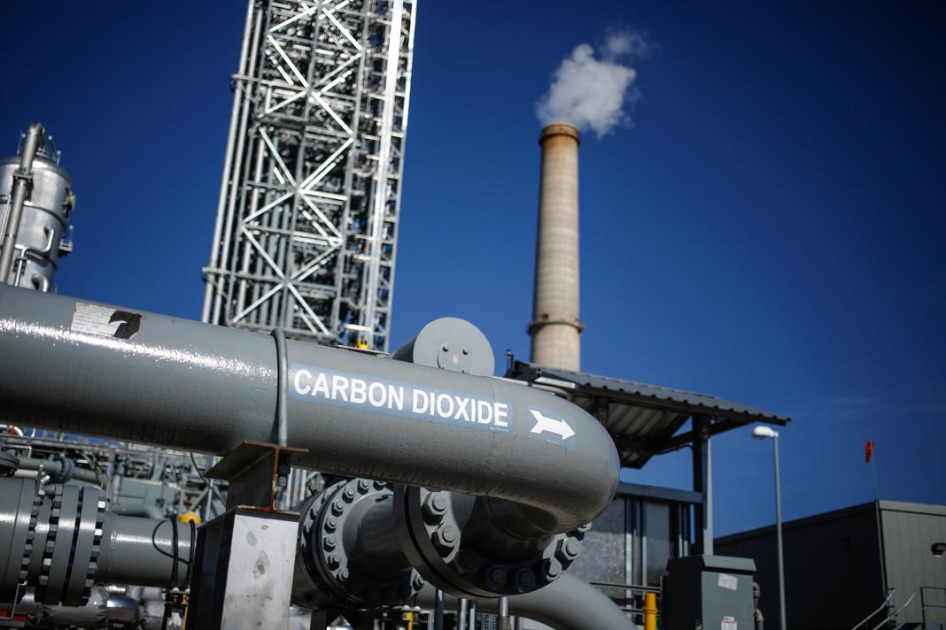 Un énorme tuyau gris avec une cheminée d'usine et le ciel bleu à l'arrière-plan (© Luke Sharrett/Bloomberg/Getty Images)