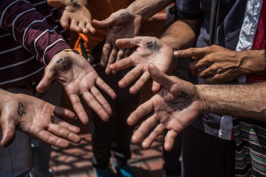 Close-up of several hands with writing on them (© Juancho Torres/Anadolu Agency/Getty Images)