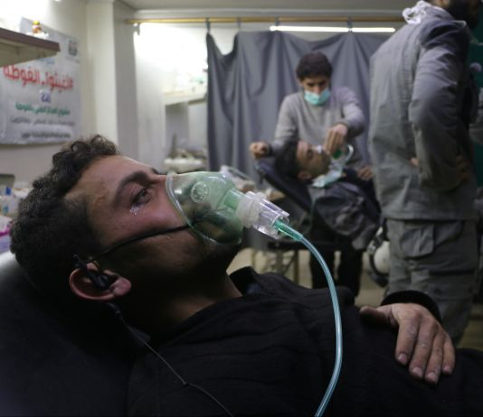 Man lying back with oxygen mask on his face (© Mohammad Al Shami/Anadolu Agency/Getty Images)