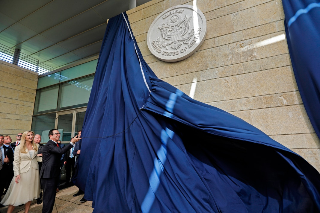 Man pulling blue curtain off of embassy seal as smiling woman and others look on (© Menahem Kahana/AFP/Getty Images)