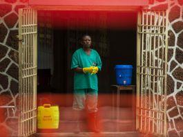 Hombre en traje sanitario con guantes y botas, de pie junto a portón abierto con un contenedor para regar al lado (© Junior Kannah/AFP/Getty Images)