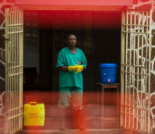 Man in scrubs standing at open gated doors wearing gloves and boots, with a sprayer beside him (© Junior Kannah/AFP/Getty Images)
