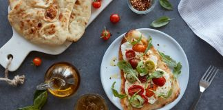 Naan pizza on white plate with tomatoes and spices around it (© American Halal Company)