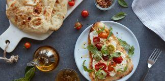 """Pizza """"naan"""" en un plato blanco con tomates y especies en torno (© American Halal Company)"""