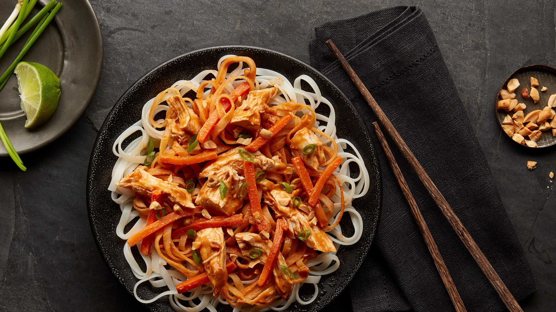 Noodles and topping on a plate with condiments and chopsticks to the side (© American Halal Company)