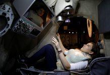 Une femme dans un simulateur spatial portant un gilet de protection (© Amir Cohen/Reuters)