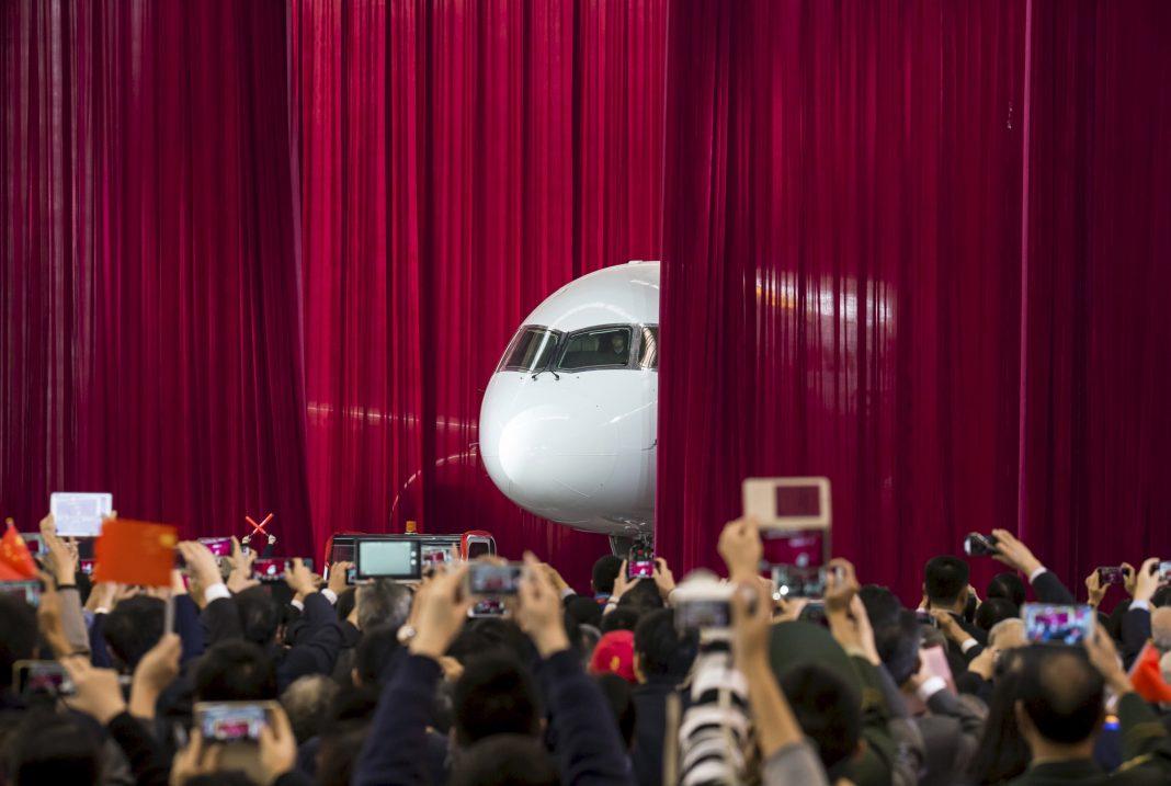 Persona fotografiando un avión que emerge tras una cortina roja (© China Daily/Reuters)