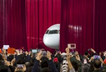 People photographing airplane emerging from behind red curtain (© China Daily/Reuters)