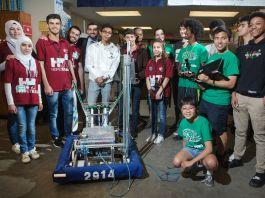 Grupo de estudiantes de pie detrás de un robot (Departamento de Estado/D.A. Peterson)