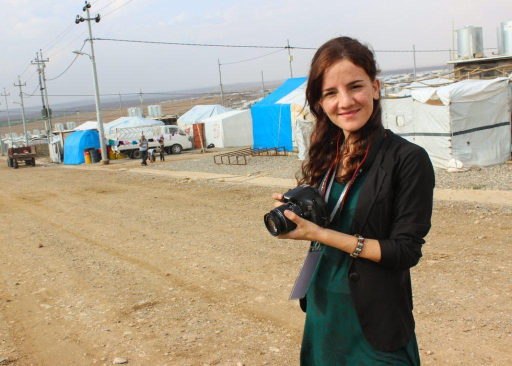 Zina Salim Hassan Hamu con una cámara frente a unas carpas (Foto cedida)