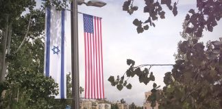 Large Israeli and U.S. flags hanging from building (State Dept.)