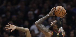 2018年6月8日,在克利夫兰进行的NBA总决赛第四场比赛中,克利夫兰骑士队的勒布朗·詹姆斯跃起投篮,金州勇士队的尼克·杨积极防守。(© AP Images)