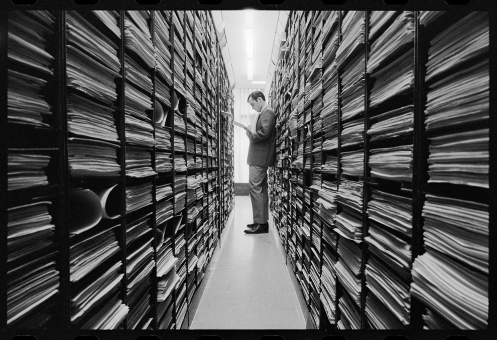 Person standing in aisle between shelves of documents (Library of Congress)